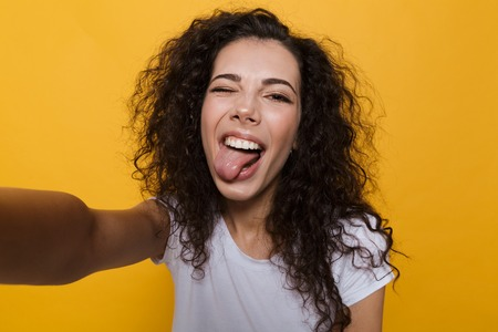 Photo pour Image of an excited happy cute young woman posing isolated over yellow background take a selfie by camera showing tongue. - image libre de droit
