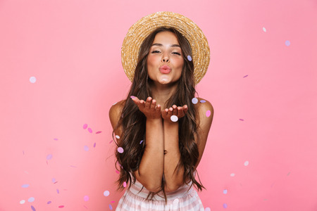 Photo pour Photo of charming woman 20s wearing straw hat laughing while standing under confetti isolated over pink background - image libre de droit