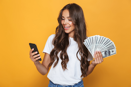 Foto de Portrait of a happy young girl with long brunette hair standing over yellow background, holding money banknotes, using mobile phone - Imagen libre de derechos