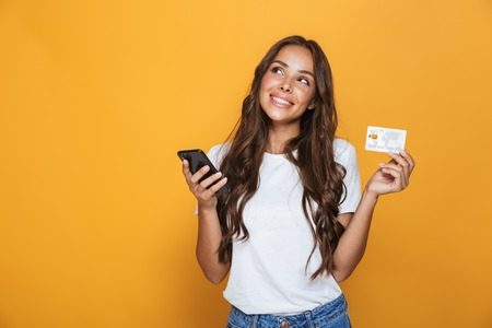 Foto de Portrait of a lovely young girl with long brunette hair standing over yellow background, holding mobile phone, showing plastic credit card - Imagen libre de derechos