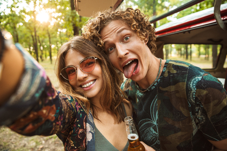 Foto de Photo of lovely hippie couple man and woman smiling and taking selfie in forest near retro minivan - Imagen libre de derechos