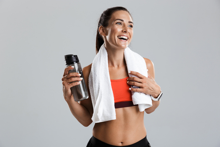 Photo pour Image of a beautiful strong smiling young sports woman posing isolated indoors drinking water with towel on neck. - image libre de droit