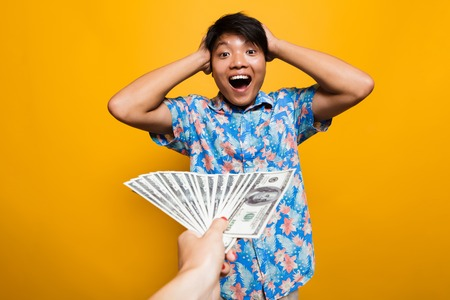 Photo pour Surprised happy asian man receiving money banknotes isolated over yellow background - image libre de droit