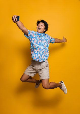 Photo pour Image of happy emotional young asian man jumping isolated over yellow background take a selfie by mobile phone. - image libre de droit