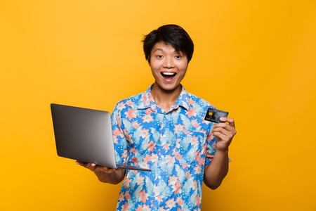 Photo pour Portrait of an excited asian man isolated over yellow background, holding laptop computer, showing plastic credit card - image libre de droit