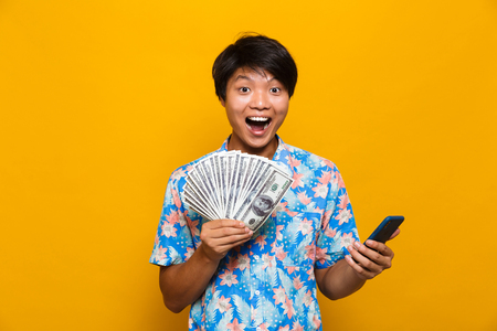 Photo for Image of happy young asian man standing isolated over yellow background holding money and using mobile phone. - Royalty Free Image