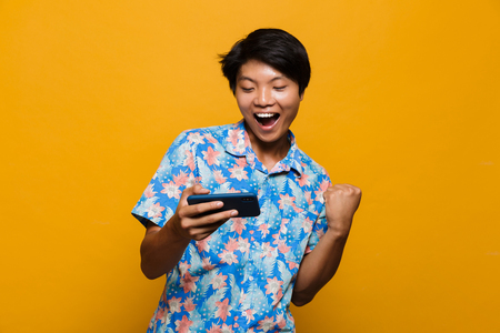 Foto de Image of an excited young asian man standing isolated over yellow background play games by mobile phone make winner gesture. - Imagen libre de derechos