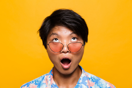 Photo pour Close up portrait of a shocked asian man in sunglasses isolated over yellow background, looking up - image libre de droit