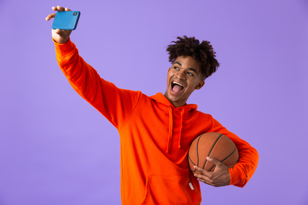 Foto de Portrait of a cheerful young african man holding a basketball isolated over violet background, takign a selfie - Imagen libre de derechos