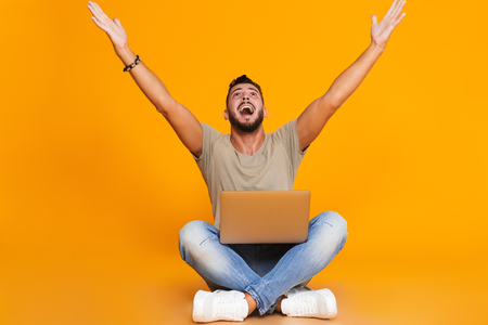 Photo for Portrait of a happy young casual man sitting isolated over orange background, holding laptop computer on his lap, celebrating success - Royalty Free Image