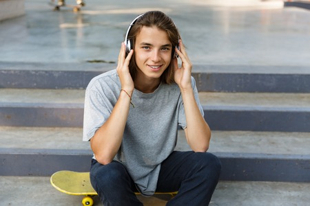 Photo pour Smiling young teenage boy spending time at the skate park, listening to music with headphones, sitting on skateboard - image libre de droit