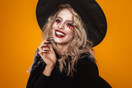 Photo pour Portrait of blonde scary woman witch in black hat looking camera and smiling isolated over orange - image libre de droit
