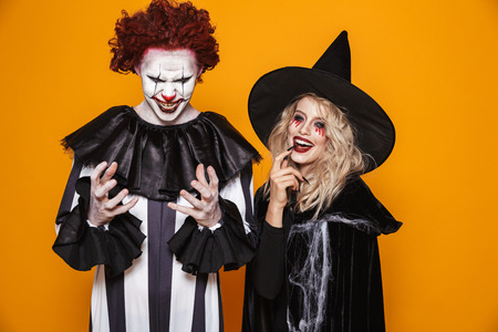 Foto de Image of witch woman and clown man wearing black costume and halloween makeup smiling at camera isolated over yellow background - Imagen libre de derechos