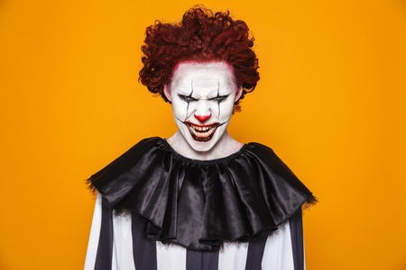 Photo for Tricky scary man clown in costume looking camera with anger and smiling isolated over orange - Royalty Free Image
