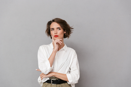 Foto de Portrait of a pensive young woman dressed in white shirt standing isolated over gray background, looking away - Imagen libre de derechos