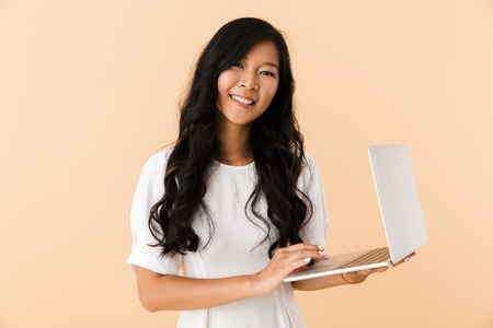 Photo pour Portrait of a happy young asian woman isolated over beige, using laptop - image libre de droit