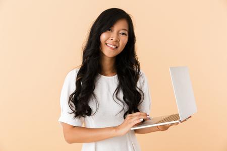 Foto de Portrait of a happy young asian woman isolated over beige, using laptop - Imagen libre de derechos