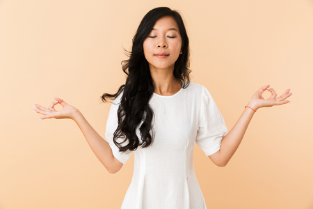 Photo pour Portrait of a smiling young asian woman isolated over beige background, meditating, eyes closed - image libre de droit
