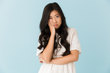 Foto für Image of young tired bored asian beautiful woman isolated over blue background. - Lizenzfreies Bild