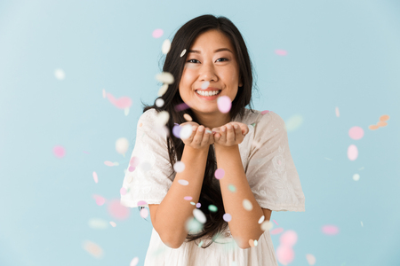 Foto de Image of asian young emotional woman isolated over blue background over confetti. - Imagen libre de derechos