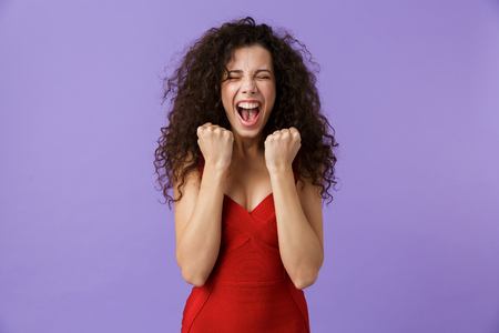 Photo for Portrait of a cheerful woman with dark curly hair wearing red dress isolated over violet background, celebrating success - Royalty Free Image