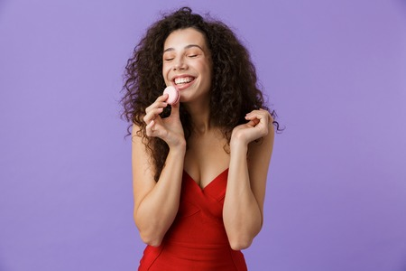 Photo for Portrait of a smiling woman with dark curly hair wearing red dress isolated over violet background, eating macaroon - Royalty Free Image
