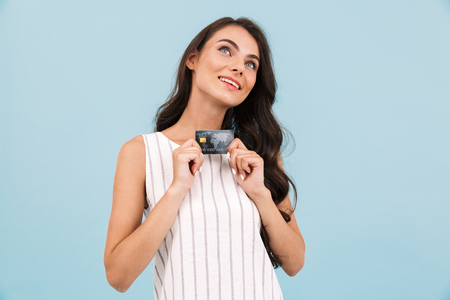 Photo pour Image of amazing young woman posing isolated over blue background wall holding credit card. - image libre de droit
