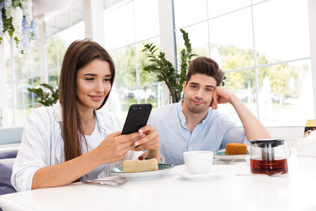 Foto de Smiling young man sitting at the cafe table while his girlfriend using mobile phone - Imagen libre de derechos