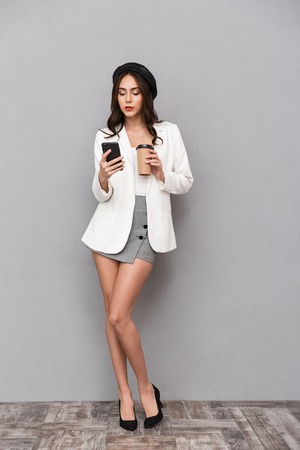 Photo for Full length portrait of a beautiful young woman dressed in mini skirt and jacket over gray background, holding cup of coffee, using mobile phone - Royalty Free Image