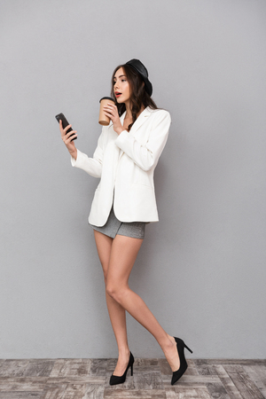 Photo for Full length portrait of a beautiful young woman dressed in mini skirt and jacket over gray background, drinking coffee, using mobile phone - Royalty Free Image