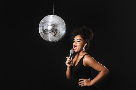 Photo for Beautiful african woman standing with silver disco ball isolated over black background, holding microphone, singing - Royalty Free Image