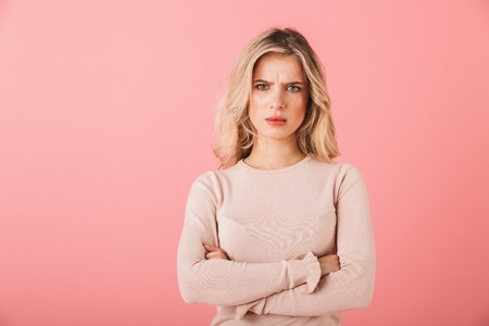 Photo pour Portrait of an upset young woman wearing sweater standing isolated over pink background, arms folded - image libre de droit