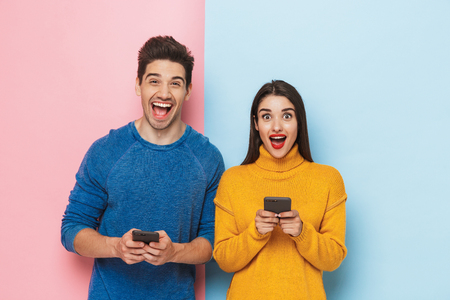 Photo pour Cheerful young couple standing isolated over two colored background, holding mobile phones - image libre de droit