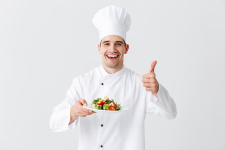Foto de Excited man chef cook wearing uniform showing fresh green salad on a plate isolated over white background, thumbs up - Imagen libre de derechos