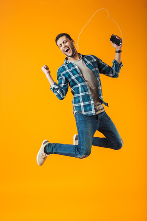 Foto de Excited young man wearing plaid shirt jumping isolated over orange background, listening to music with earphones and mobile phone - Imagen libre de derechos