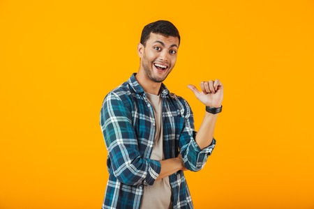 Foto de Cheerful young man wearing plaid shirt standing isolated over orange background, pointing finger at himself - Imagen libre de derechos