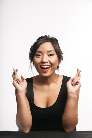 Foto per Pretty young asian woman sitting at the table isolated over white background, holding fingers crossed for good luck - Immagine Royalty Free