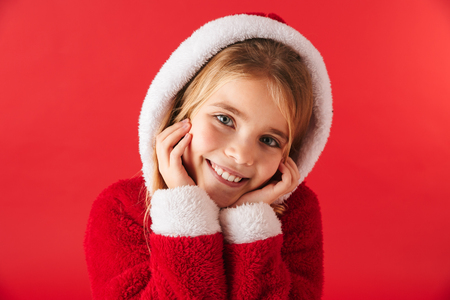 Foto de Cute cheerful little girl wearing Christmas costume isolated over red background - Imagen libre de derechos