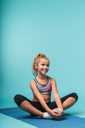 Photo pour Cheerful young sports girl sitting on a fitness mat doing yoga exercises isolated over blue background - image libre de droit