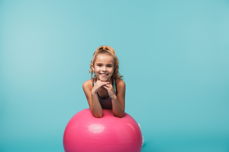 Foto de Cheerful little girl wearing sport clothes leaning on a fitness ball isolated over blue background - Imagen libre de derechos