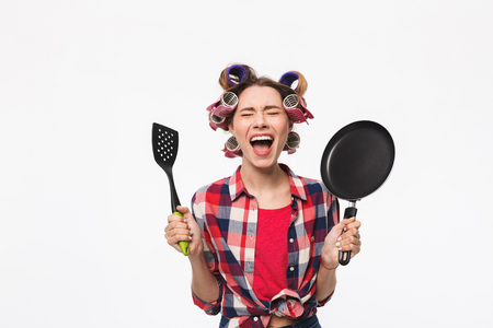 Photo pour Angry housewife with curlers in hair standing isolated over white background, holding frying pan - image libre de droit