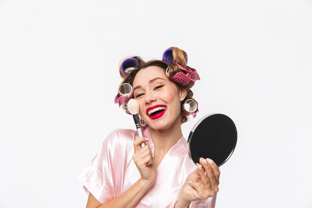 Photo for Beautiful housewife with curlers in hair wearing robe standing isolated over white background, applying makeup with a brush - Royalty Free Image
