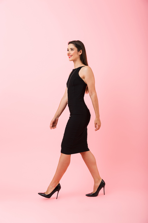 Photo for Full lengthside view portrait of a beautiful young woman wearing black dress walking isolated over pink background, celebrating success - Royalty Free Image