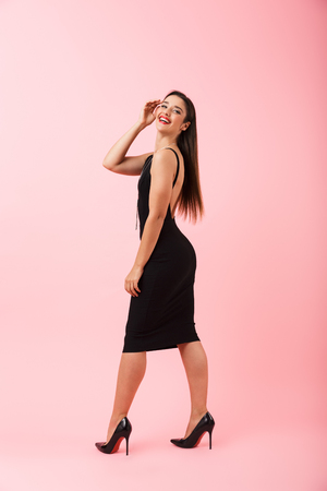 Photo pour Full length portrait of a beautiful young woman wearing black dress standing isolated over pink background, posing - image libre de droit