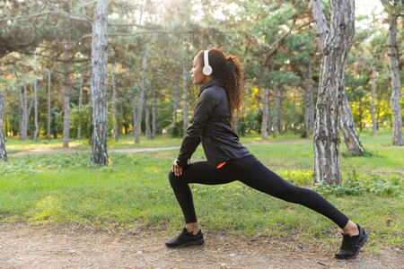 Foto de Image of sportswoman 20s wearing black tracksuit working out and stretching body in green park - Imagen libre de derechos