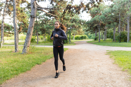 Photo pour Image of young woman 20s wearing black tracksuit working out while running through green park - image libre de droit