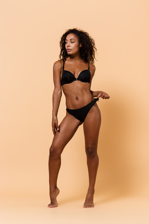 Photo pour Beauty portrait of african american girl 20s wearing black lingerie standing isolated over beige background - image libre de droit