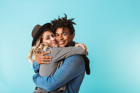 Photo pour Smiling young multiracial couple wearing scarves standing isolated over blue background, hugging - image libre de droit