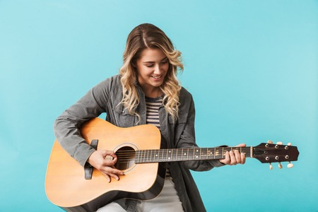 Photo for Smiling young girl playing a guitar while sitting isolated over blue - Royalty Free Image