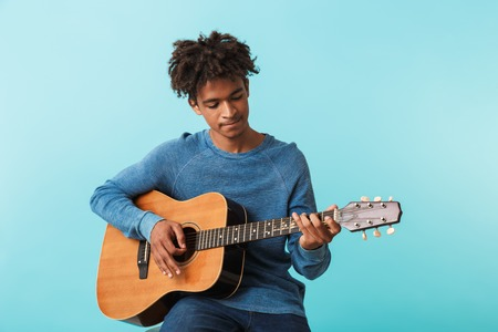 Photo for Handsome young african man playing a guitar while sitting isolated over blue - Royalty Free Image